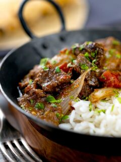 Portrait image of an onion rich beef dopiaza curry served in an iron karahi with rice and a coriander garnish