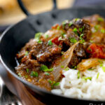 Portrait image of an onion rich beef dopiaza curry served in an iron karahi with rice and a coriander garnish and a text overlay