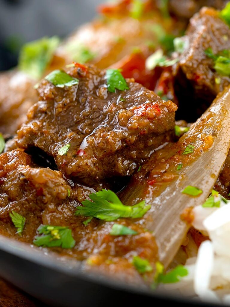 Portrait close up image of an onion rich beef dopiaza curry served in an iron karahi with rice and a coriander garnish