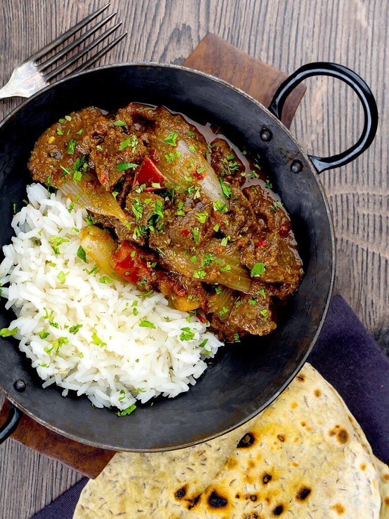 Portrait overhead image of an onion rich beef dopiaza curry served in an iron karahi with rice and a coriander garnish