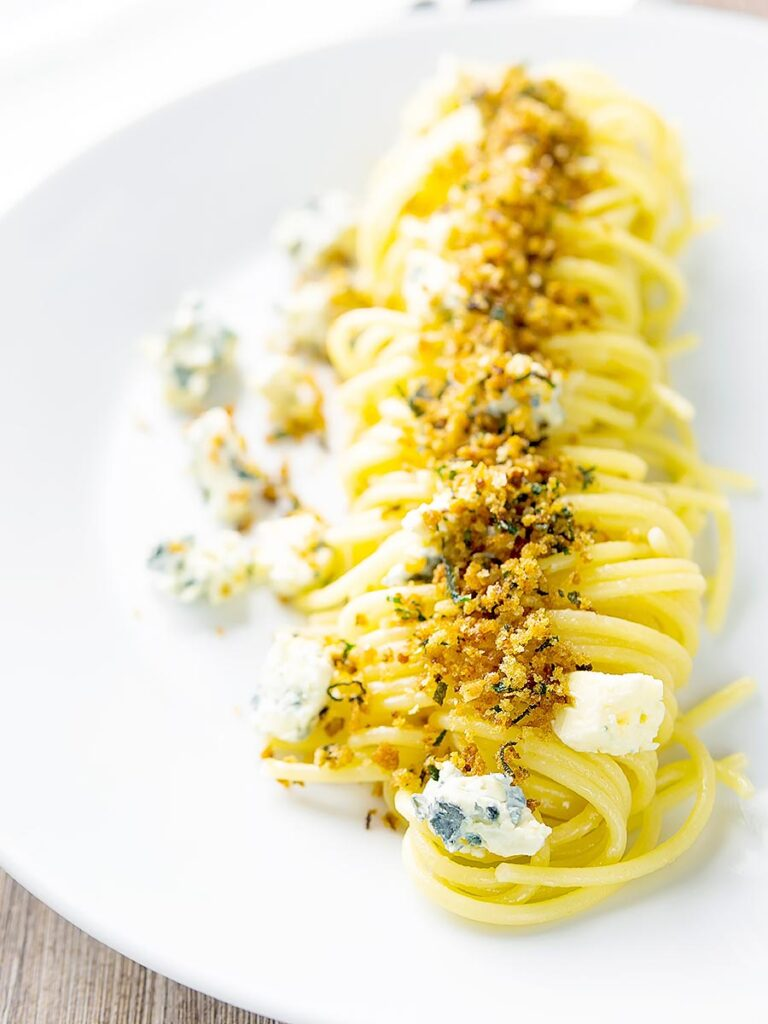 Portrait image of a blue cheese pasta recipe featuring spaghetti coated in garlic butter, a buttery sage crumb and Gorgonzola cheese