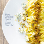 Portrait overhead image of a blue cheese pasta recipe featuring spaghetti coated in garlic butter, a buttery sage crumb and Gorgonzola cheese with a text overlay