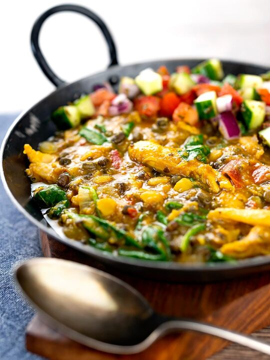 Portrait image of an Indian Chicken Dhansak lentil curry served in a cast iron karahi with a kachumber salad