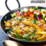 Portrait image of an Indian Chicken Dhansak lentil curry served in a cast iron karahi with a kachumber salad with a text overlay