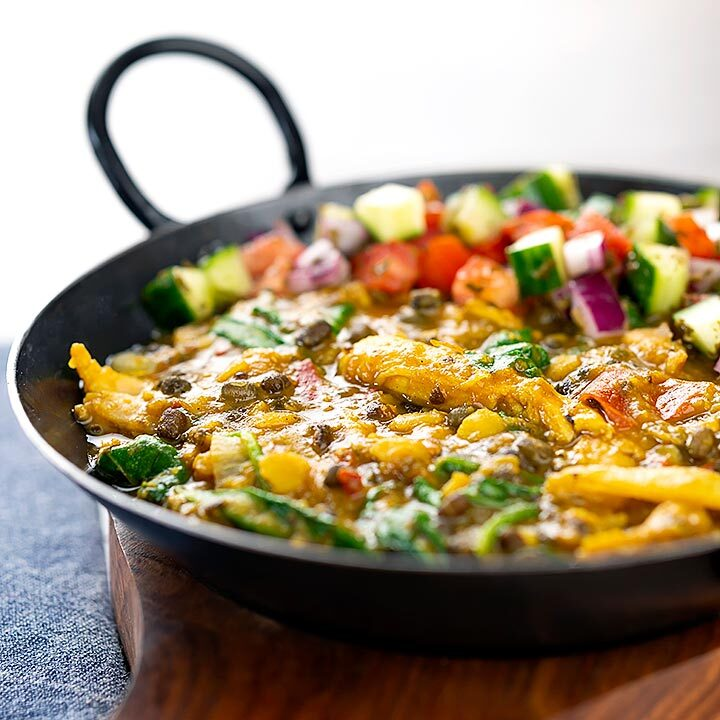 Square image of an Indian Chicken Dhansak lentil curry served in a cast iron karahi with a kachumber salad