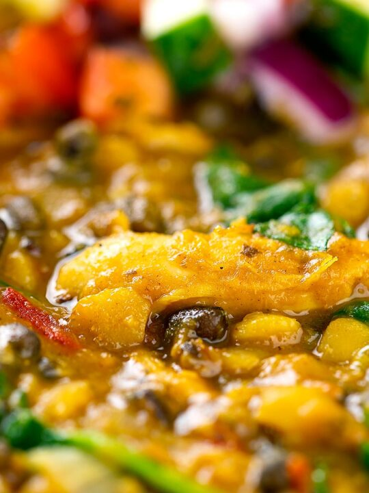 Portrait close up image of an Indian Chicken Dhansak lentil curry served with a kachumber salad
