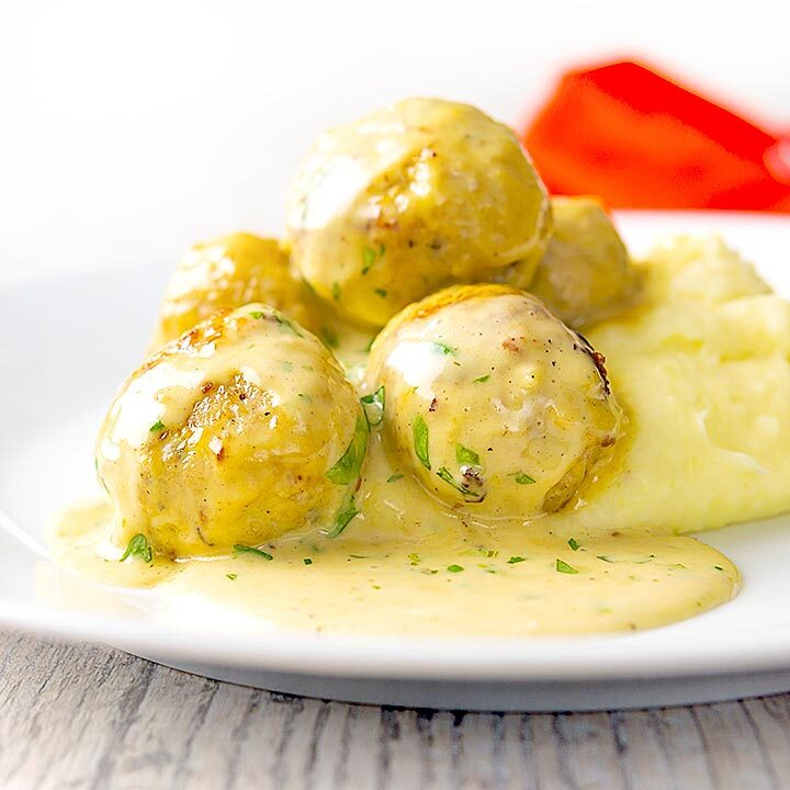 Square image of chicken meatballs in a creamy honey and mustard sauce served with mashed potatoes