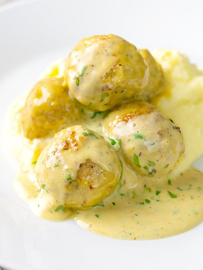 Portrait image of chicken meatballs in a creamy honey and mustard sauce with text overlay served with mashed potato