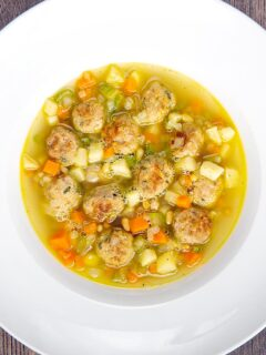 Portrait overhead image of an simple pork meatball soup in a golden vegetable broth served in a white bowl
