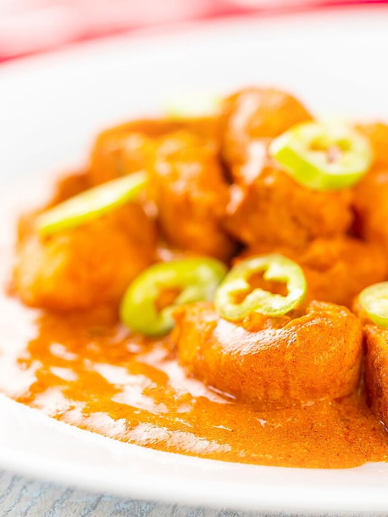 Portrait image of a Hungarian fish paprikash or harcsapaprikash served on a white plate in a silky paprika rich sauce