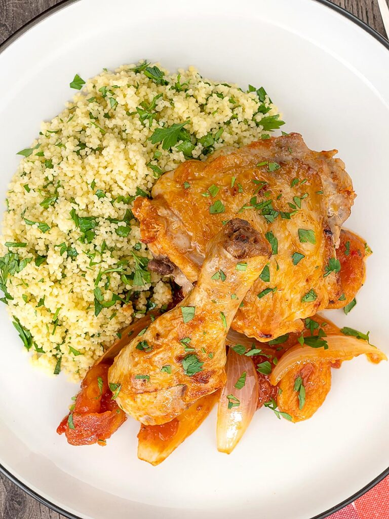 Portrait overhead image of a Moroccan influenced chicken tagine with dried apricots made with chicken drumsticks and thighs served with buttered couscous