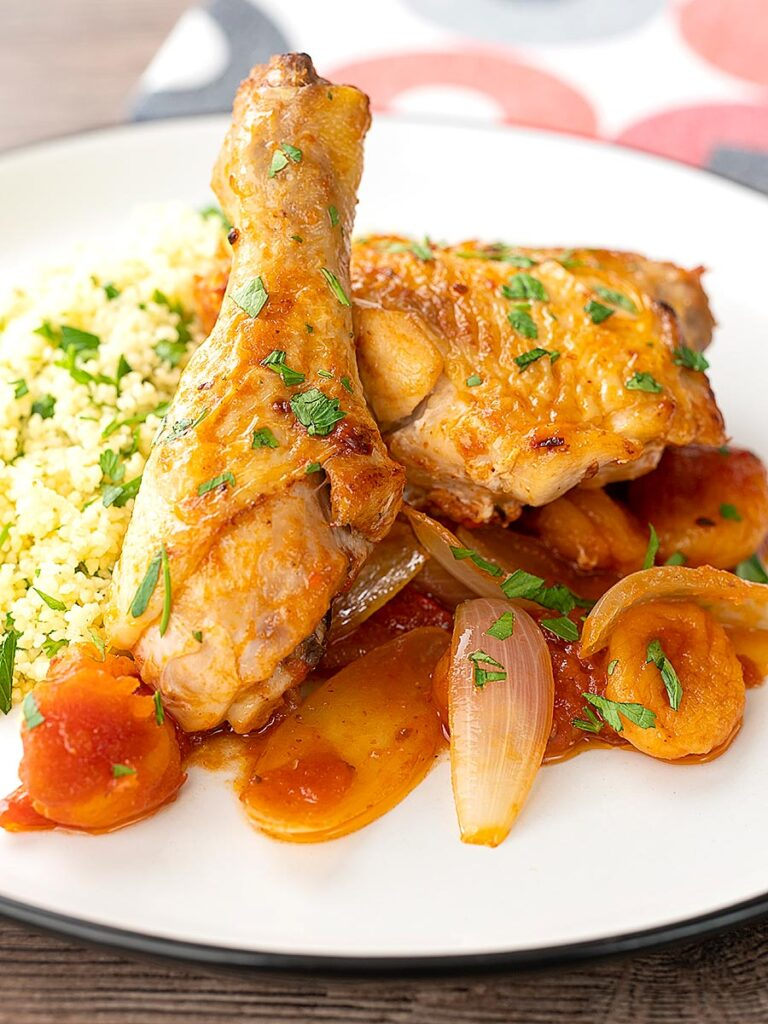 Portrait close up image of a Moroccan influenced chicken tagine with dried apricots made with chicken drumsticks and thighs served with buttered couscous