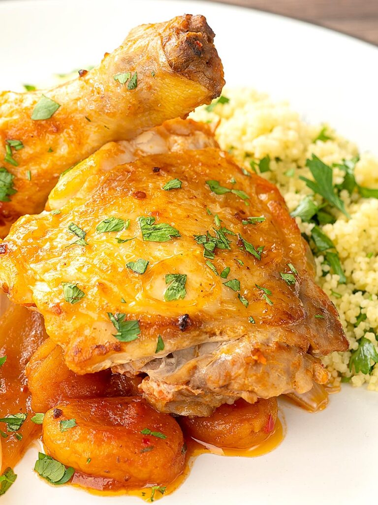 Portrait image of a Moroccan influenced chicken tagine with dried apricots made with chicken drumsticks and thighs served with buttered couscous