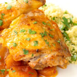 Portrait image of a Moroccan influenced chicken tagine with dried apricots made with chicken drumsticks and thighs served with buttered couscous with text overlay