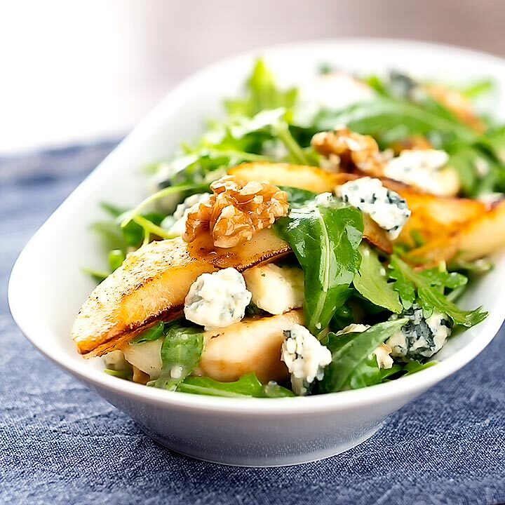 Square image of a pear and blue cheese salad with rocket (arugula) and walnuts served in a white bowl
