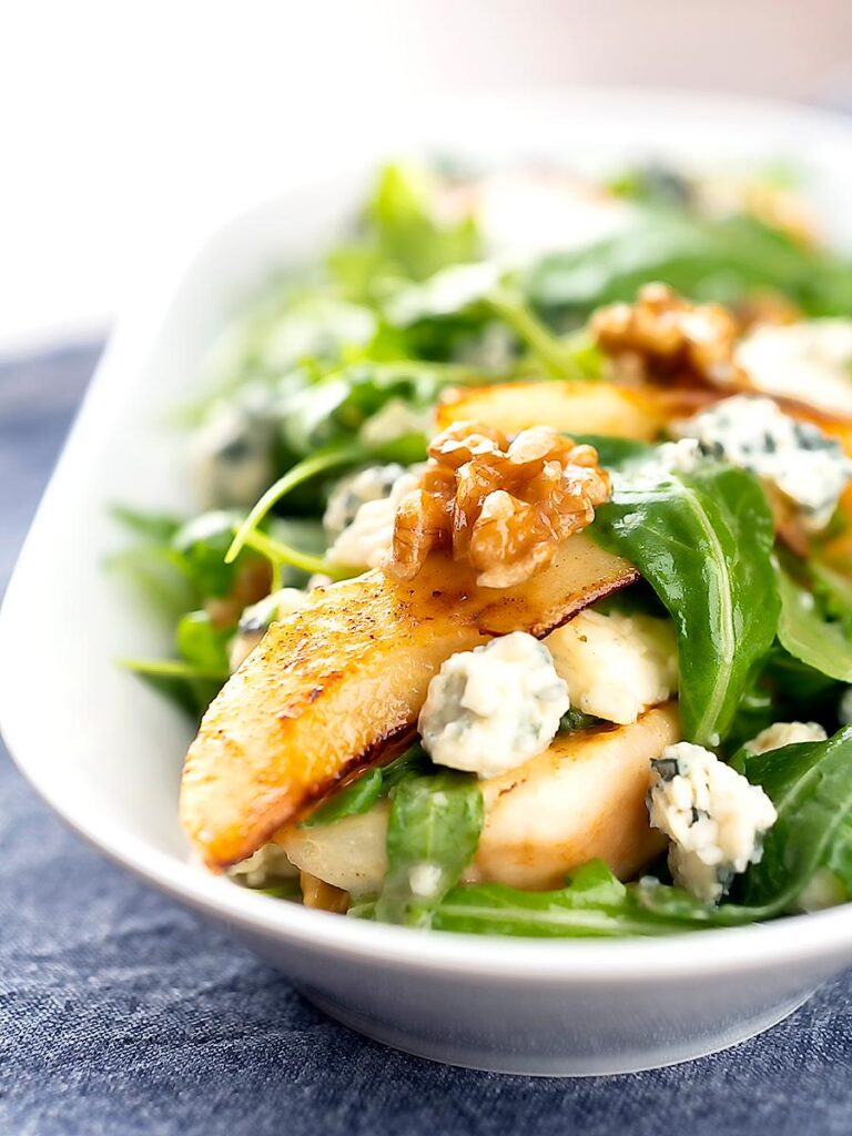 Portrait image of a pear and blue cheese salad with rocket (arugula) and walnuts served in a white bowl