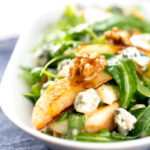 Portrait image of a pear and blue cheese salad with rocket (arugula) and walnuts served in a white bowl with a text overlay
