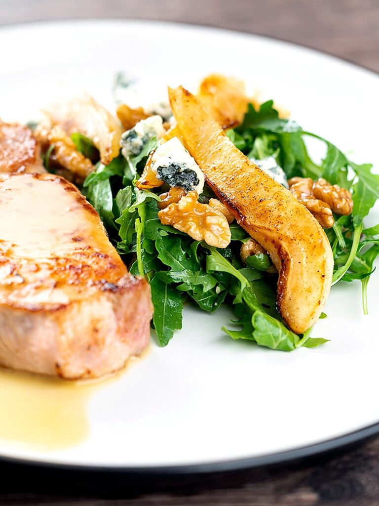 Portrait image of a pear and blue cheese salad with rocket (arugula) and walnuts served as a side dish to a pork chop