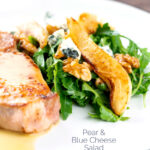 Portrait image of a pear and blue cheese salad with rocket (arugula) and walnuts served as a side dish to a pork chop with a text overlay