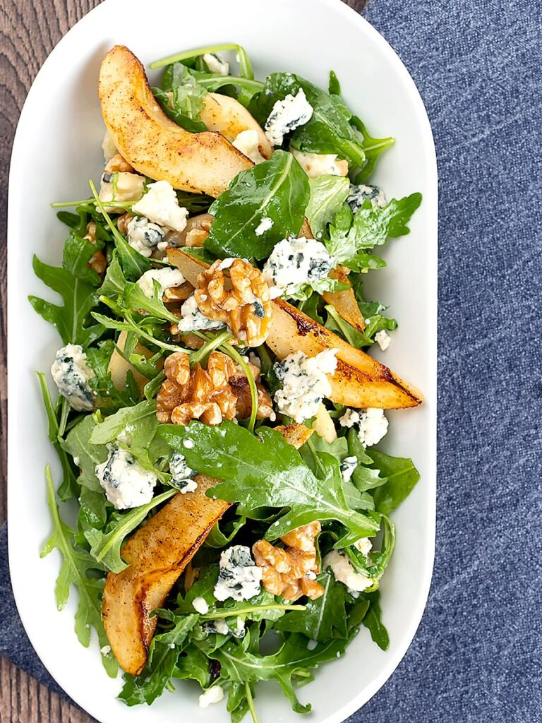 Portrait overhead image of a pear and blue cheese salad with rocket (arugula) and walnuts served in a white bowl
