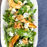 Portrait overhead image of a pear and blue cheese salad with rocket (arugula) and walnuts served in a white bowl with a text overlay