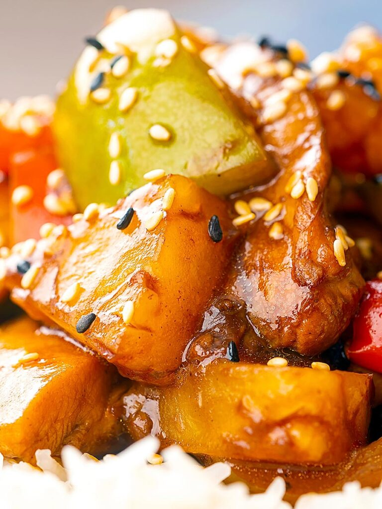 Portrait close up image of a Chinese influenced sweet and sour pineapple chicken dish served with white rice