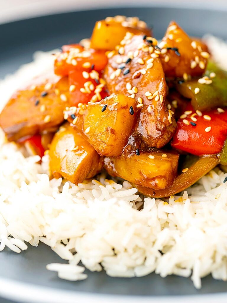 Portrait image of a Chinese influenced sweet and sour pineapple chicken dish served with white rice