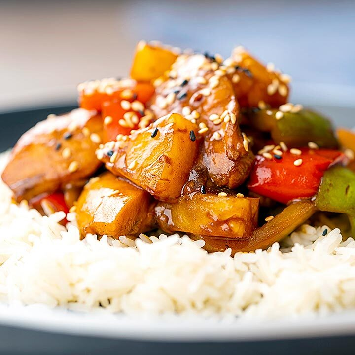 Square image of a Chinese influenced sweet and sour pineapple chicken dish served with white rice