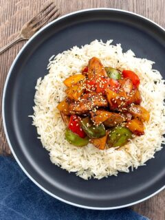 Portrait overhead image of a Chinese influenced sweet and sour pineapple chicken dish served with white rice
