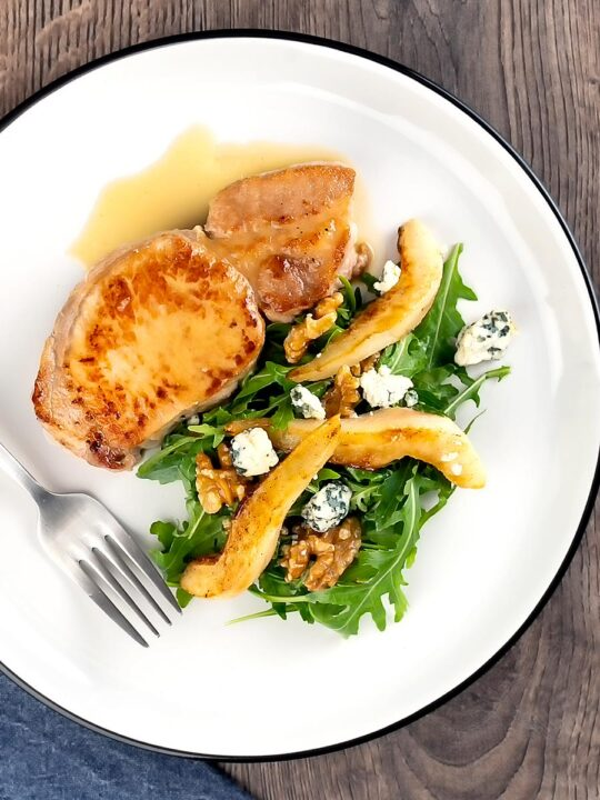 Portrait overhead image of a pork loin steak in a cider sauce served on a white plate with a pear and blue cheese salad