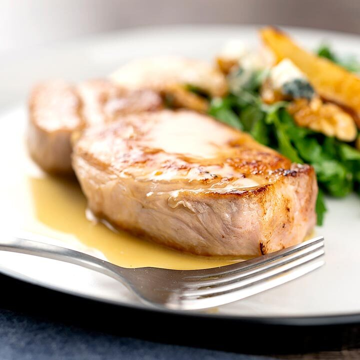 Square image of a pork loin steak served on a white plate with a cider sauce and side salad
