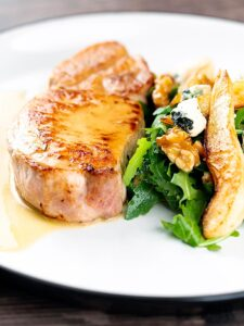 Portrait close up image of a pork loin steak in a cider sauce served on a white plate with a pear and blue cheese salad