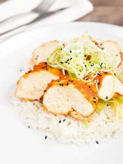Portrait image of a sliced steamed chicken breast cooked in a spicy Korean gochujang marinade served on white rice