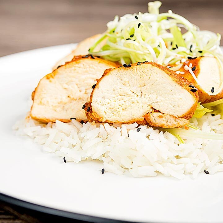 Square image of a sliced steamed chicken breast cooked in a spicy Korean gochujang marinade served on white rice