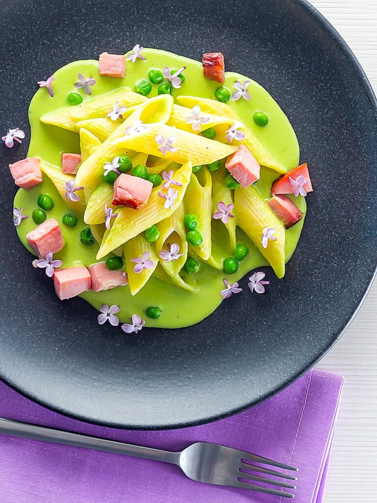Portrait overhead image of ham and pea pasta using penne rigatoni and edible lilac flowers as garnish