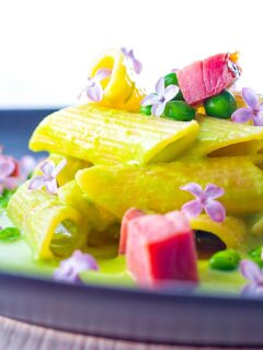 Portrait close up image of ham and pea pasta using penne rigatoni and edible lilac flowers as garnish