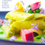 Portrait close up image of ham and pea pasta using penne rigatoni and edible lilac flowers as garnish with text overlay