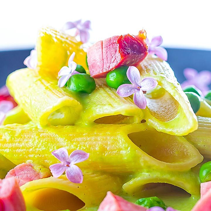 Square image of ham and pea pasta using penne rigatoni and edible lilac flowers as garnish