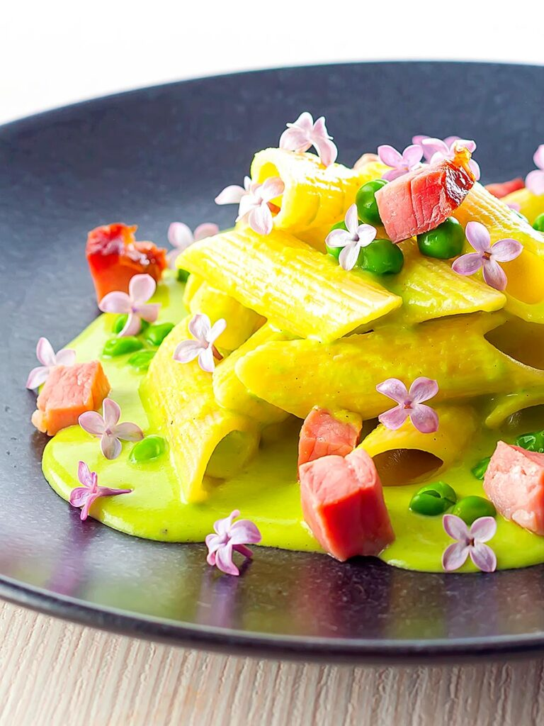 Portrait image of ham and pea pasta using penne rigatoni and edible lilac flowers as garnish
