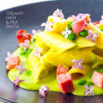 Portrait image of ham and pea pasta using penne rigatoni and edible lilac flowers as garnish with text overlay