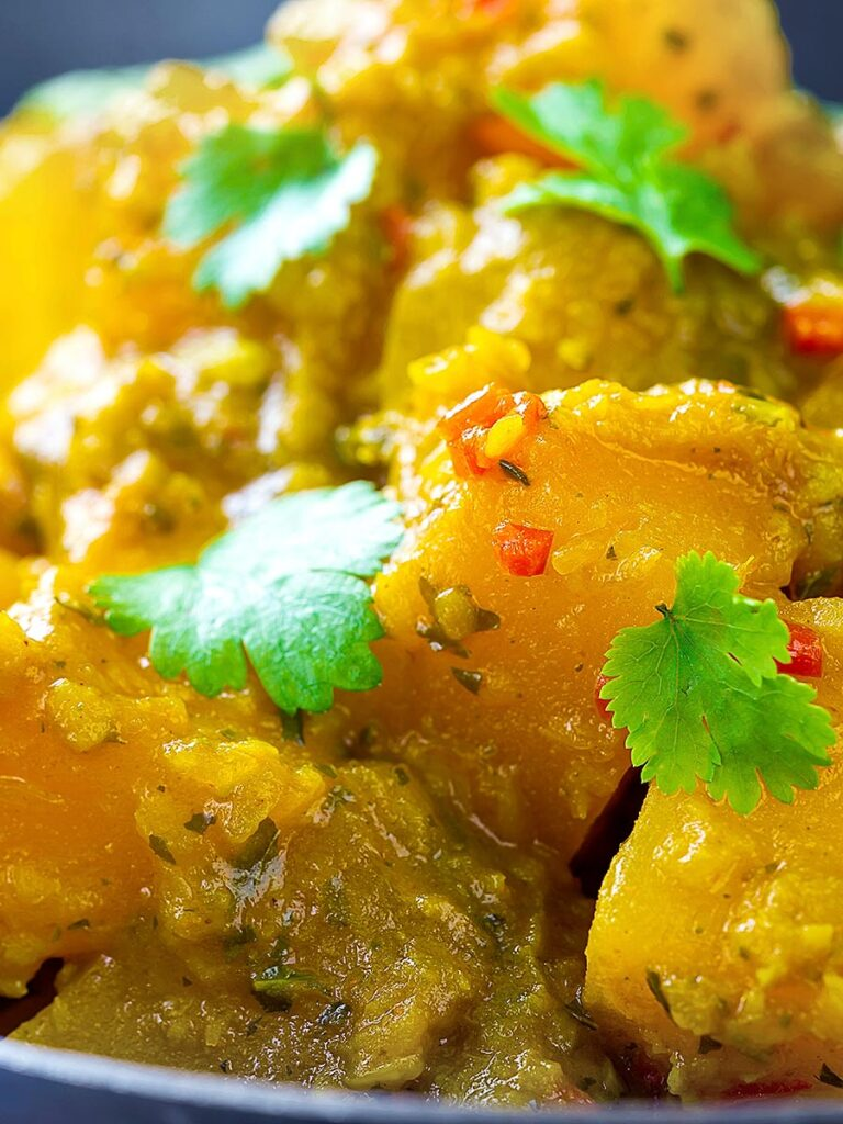 Portrait close up image of a Burmese influenced vegan pumpkin curry served with white rice and fresh coriander