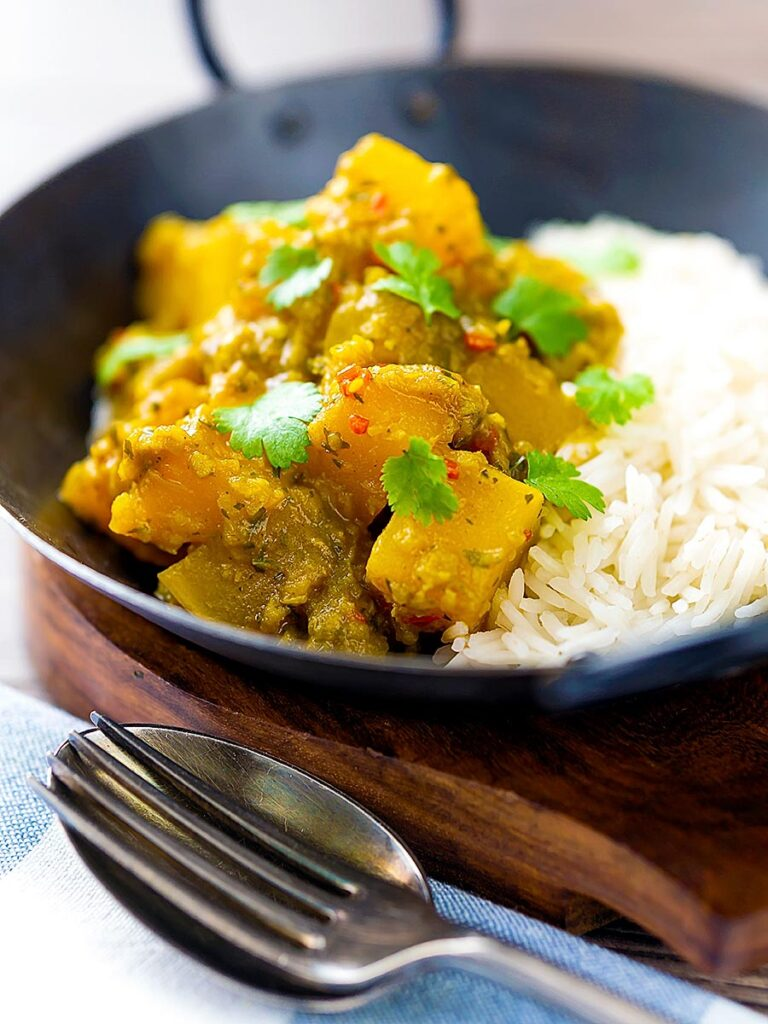 Portrait image of a Burmese influenced vegan pumpkin curry served with white rice and fresh coriander