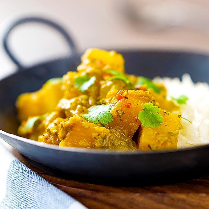 Square image of a Burmese influenced vegan pumpkin curry served with white rice and fresh coriander