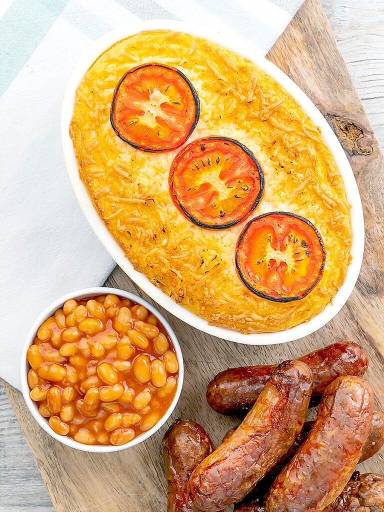 Portrait overhead image of cheese and potato pie bake topped with tomato slices and served with sausages and baked beans