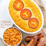 Portrait overhead image of cheese and potato pie bake topped with tomato slices and served with sausages and baked beans featuring a text overlay