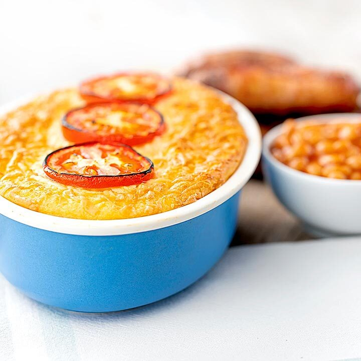 Square image of cheese and potato pie bake served with sausages and baked beans