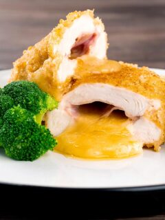 Portrait image of chicken cordon bleu, cheese and ham stuffed chicken breast cut open to show oozing cheese served with broccoli