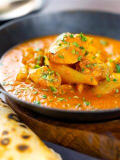 Portrait image of a chicken jalfrezi curry with a coriander garnish served in an iron karahi bowl and chapatis