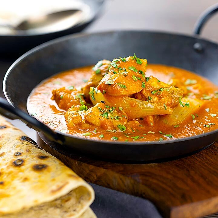 Square image of a chicken jalfrezi curry with a coriander garnish served in an iron karahi bowl and chapatis and boiled rice featuring