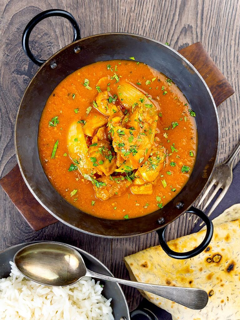 Portrait overhead image of a chicken jalfrezi curry with a coriander garnish served in an iron karahi bowl and chapatis and boiled rice